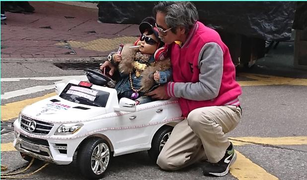 著名的旺角女人街,街邊檔接近中午時分已經搭好。一男士正在把小司機抱進他的模型開篷車。(木子/大紀元)