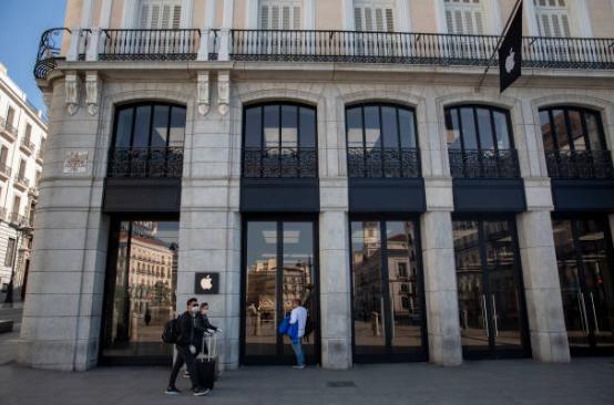 3月14日,戴口罩的民眾在西班牙馬德里一家關張的蘋果實體店外。(Pablo Blazquez Dominguez/Getty Images)