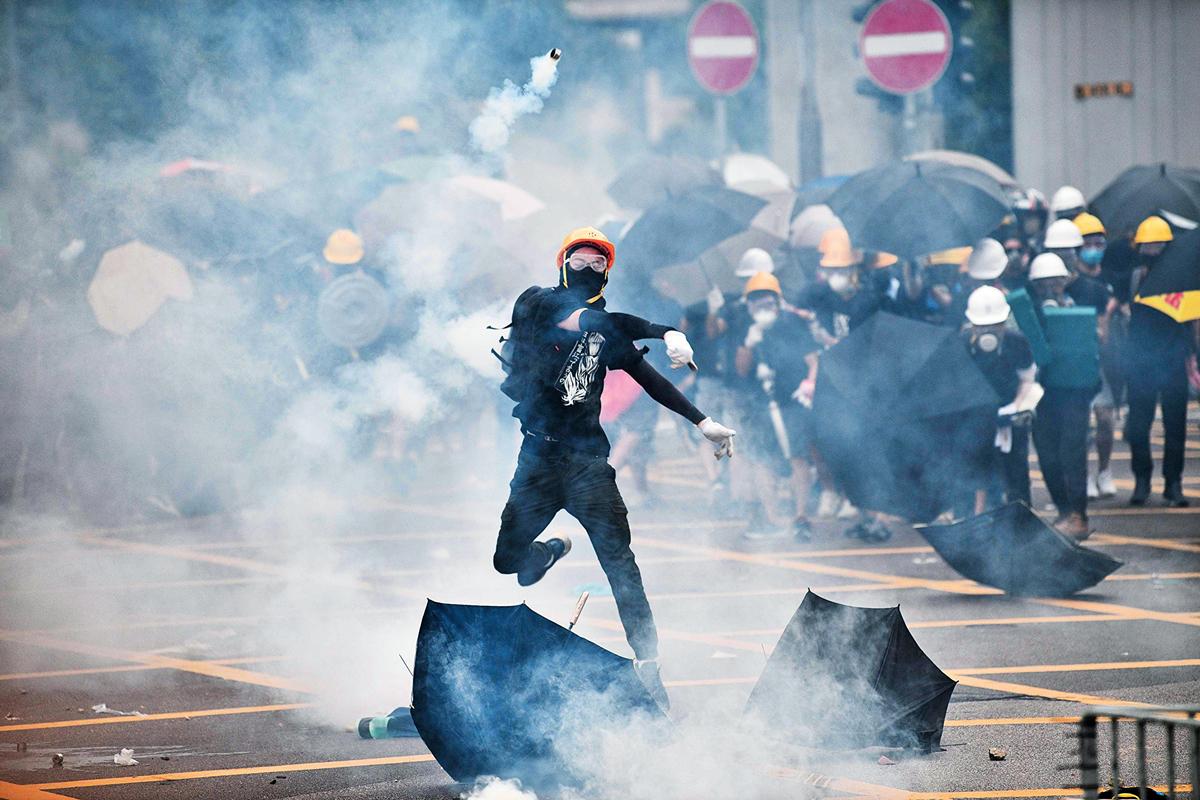 2019年7月27日,香港民眾來到元朗集會,抗議警察暴力執法。圖為一青年把警察發射的催淚彈扔回去。(Getty Images)
