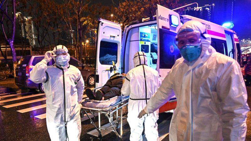 圖為武漢醫護人員收治患者。(HECTOR RETAMAL/AFP via Getty Images)