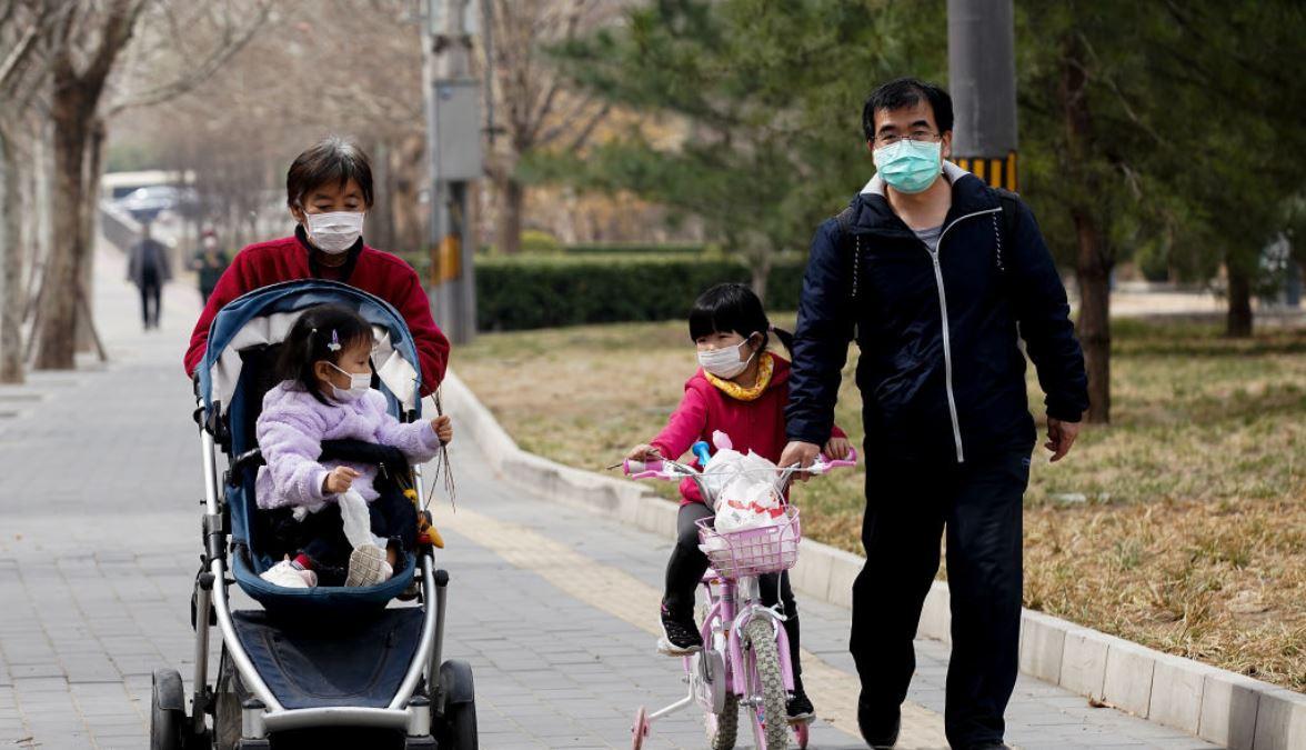 圖為北京一個家庭一家老小到一個公園裏散步時都戴上防護口罩預防被中共病毒(新冠狀病毒)感染。(Lintao Zhang/Getty Images)
