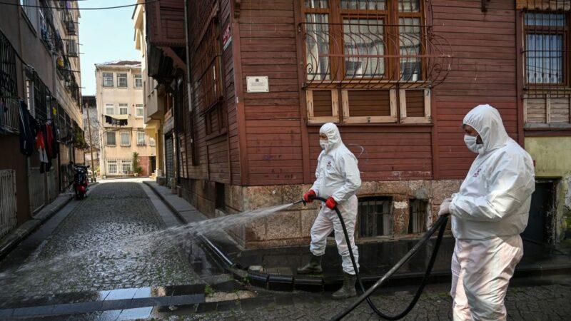 2020年3月20日,土耳其法提赫市政府的成員對伊斯坦布爾Zeyrek區的一條街道進行消毒和沖洗。(OZAN KOSE/AFP via Getty Images)