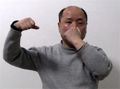 影片截圖,胡林演示被捏鼻子,打腦袋。(明慧網)