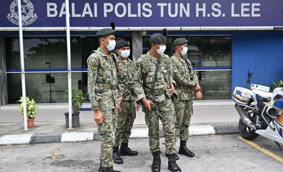 為了應對中共肺炎(俗稱武漢肺炎、新冠肺炎)的傳播,2020年3月22日馬來西亞吉隆坡的軍人戴著防護口罩離開警察局,準備外出執勤。(MOHD RASFAN/AFP via Getty Images)