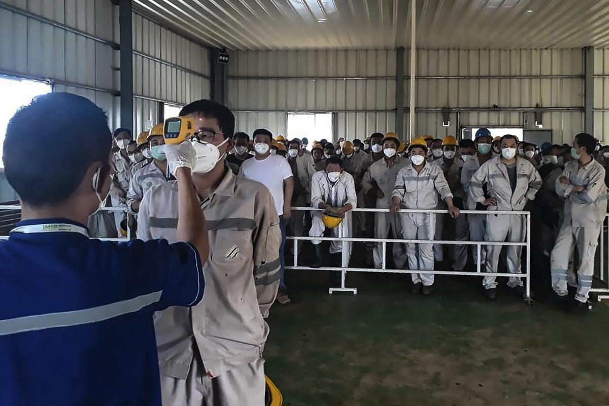 疫情洶洶,中共編造疫情收尾的虛假消息,急於復工。圖為排隊量體溫的工人。(STR/AFP via Getty Images)