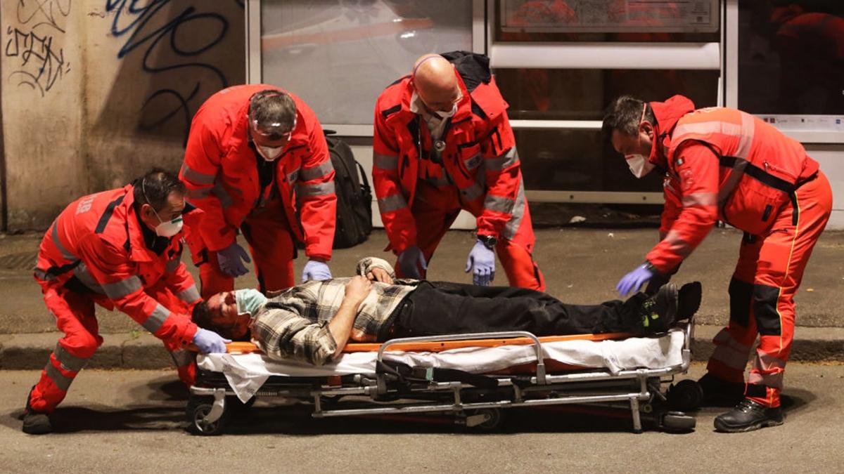 意大利是中共病毒疫情重災區,圖為意大利醫護人員收治一名倒在街上的男子。(Marco Di Lauro/Getty Images)