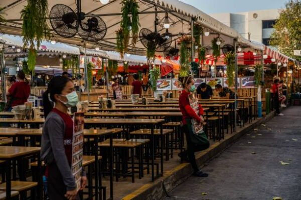 2020年3月11日,因中共肺炎疫情蔓延,曼谷最近2月份的遊客數量與去年相比下降了44.3%。圖為,泰國餐館工作人員站在街頭招呼客人。(Lauren DeCicca/Getty Images)