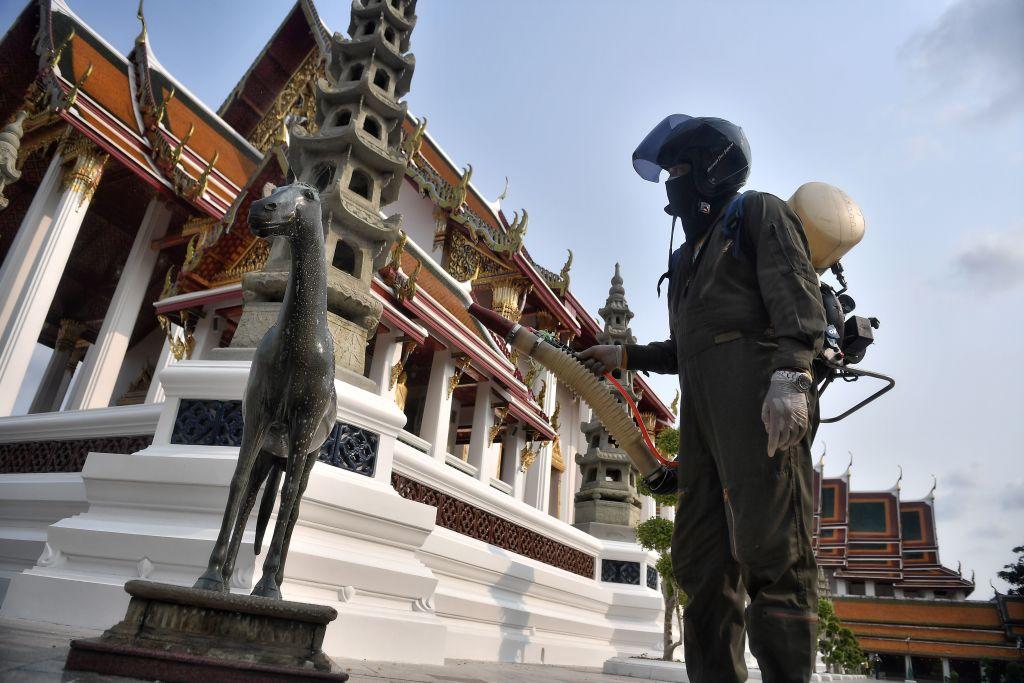 2020年3月17日,一名消毒人員在曼谷寺廟噴灑消毒液。(LILLIAN SUWANRUMPHA/AFP via Getty Images)