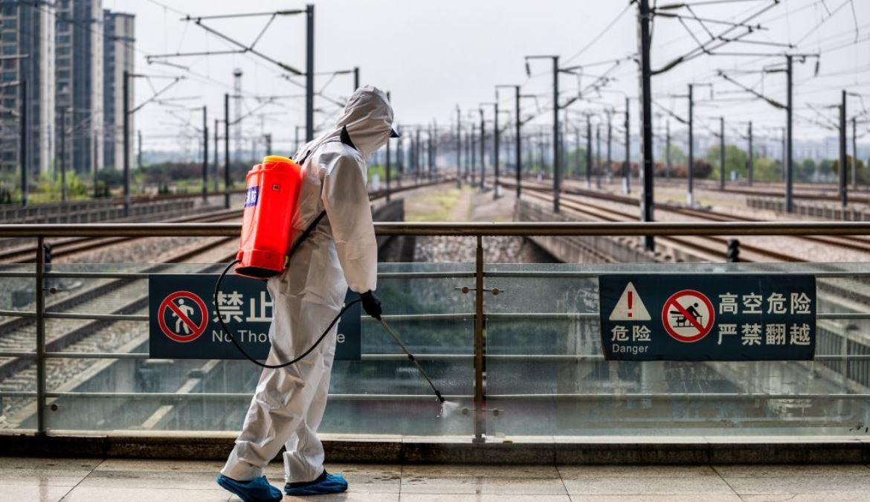 一名身穿防護服的工作人員,2020年3月24日在中國湖北省武漢市的武漢火車站噴灑消毒劑。(STR/AFP via Getty Images)