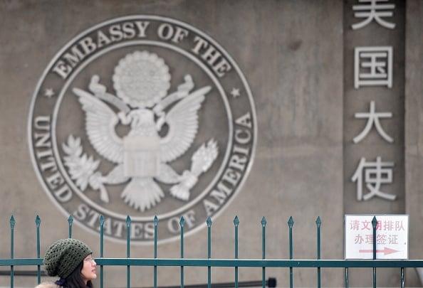 2010年2月6日,一女性從北京的美國大使館門前經過。(FREDERIC J. BROWN/AFP via Getty Images)