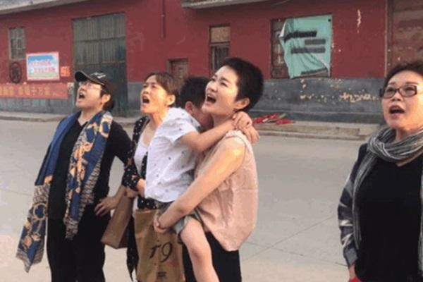 王全璋遭羈押近四年,李文足(抱孩子者)和友人在監獄外呼喊丈夫的名字。(推特圖片)
