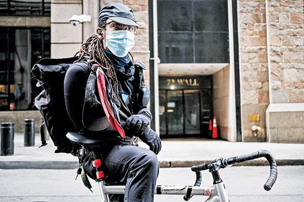 3月20日,一名戴口罩的送餐人員在紐約證券交易所前停步。(Getty Images)