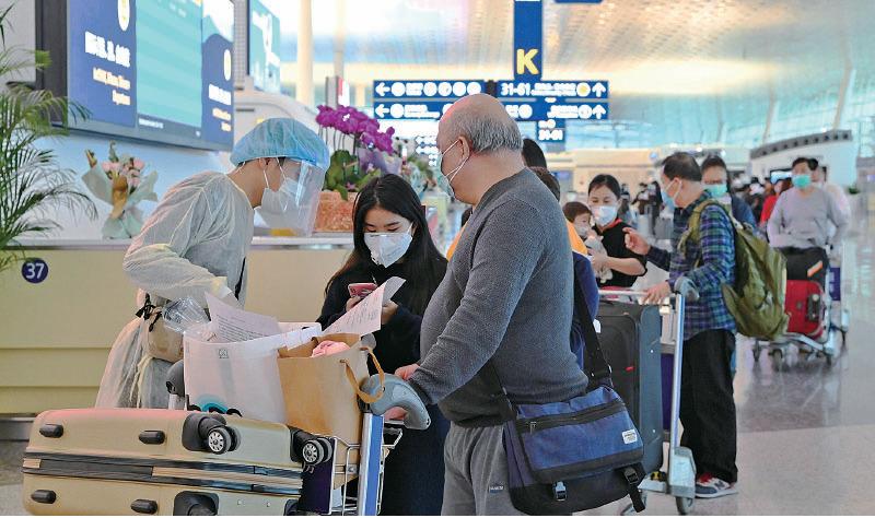 政府昨日派第二批包機,接載滯鄂香港居民回港。圖為乘坐首班專機回港的港人在武漢天河國際機場排隊準備登機。(政府新聞處)