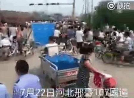 村民將所有在泄洪中被淹死的村民遺體抬到了107國道上進行抗議。(視像截圖)