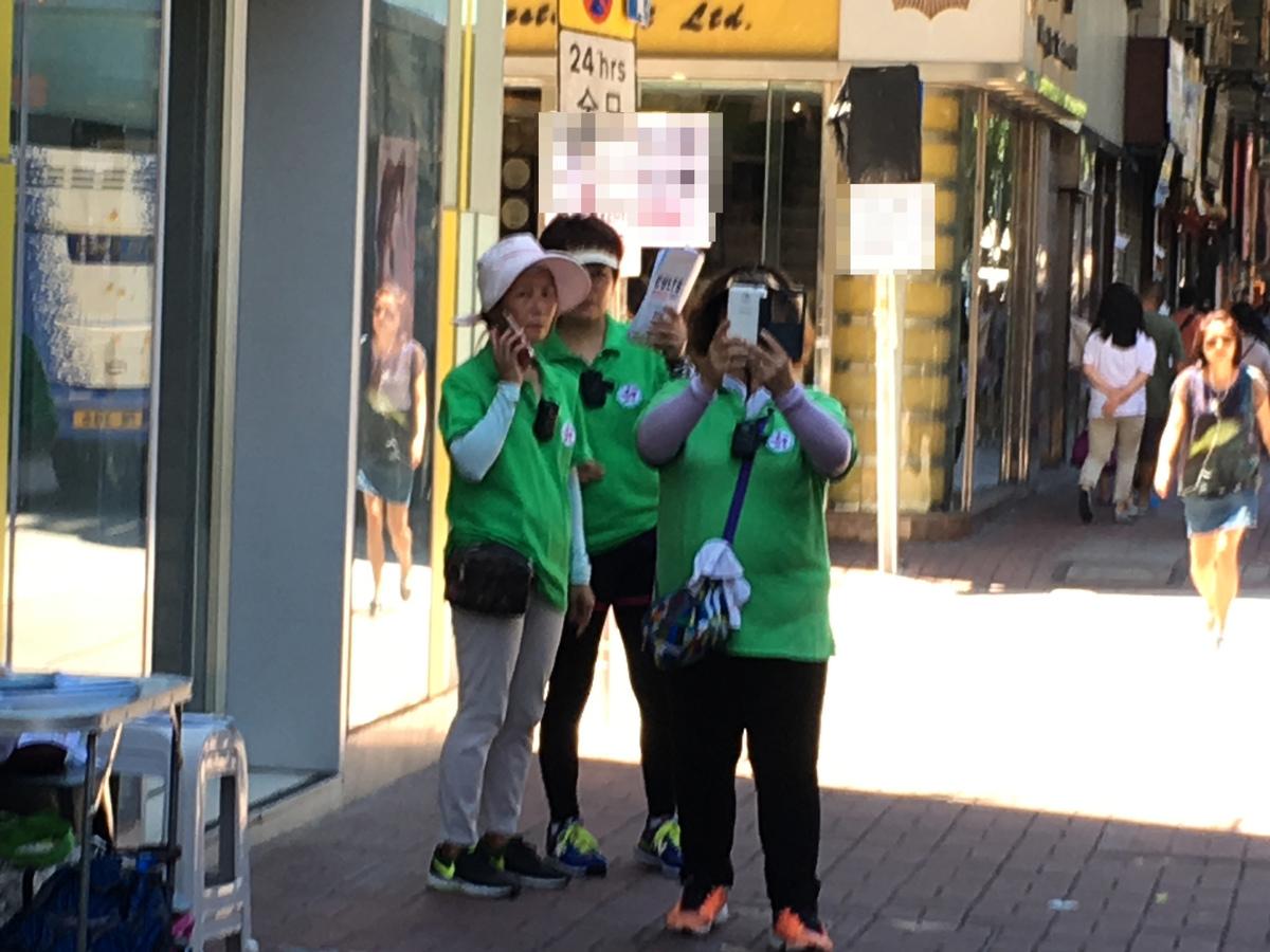 7月23日,在新唐人舉辦的「全世界中國古典舞大賽」亞太區初賽場館——麥花臣場館外,數名身穿綠色統一制服的青關會成員,派發污衊單張。不過他們均戴上帽子,將帽子壓低遮面。一見到記者在場拍攝,更用手機或手上的單張,試圖躲避和遮掩。(梁珍/大紀元)