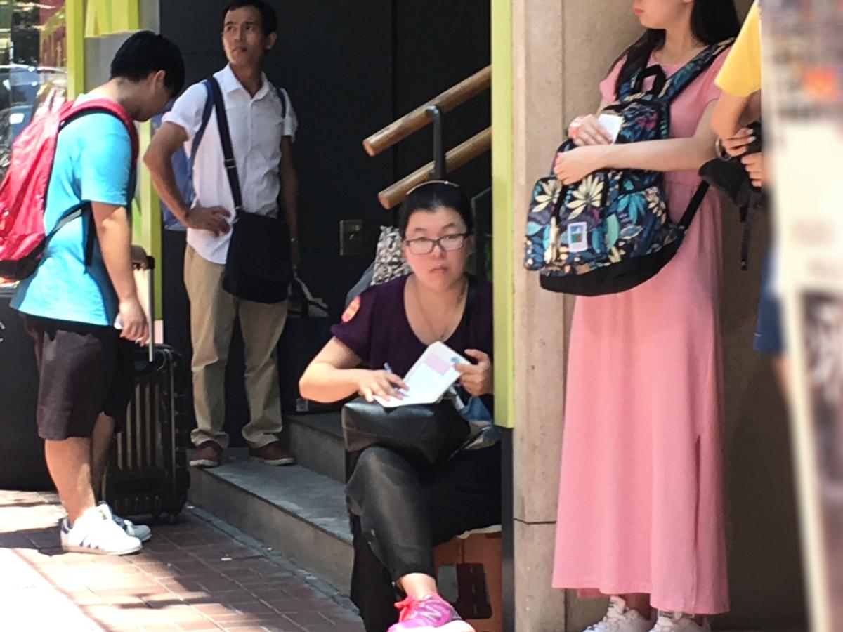 麥花臣場館外的奶路臣街上,民交協懸掛污衊法輪功的所謂「圖片展」。今次更將污衊圖片易拉架貼近售票處,旁邊還有一名身上貼有民交協標誌的女成員,搬凳坐在大街上,用筆記記錄有誰在觀看展板,或者到場買票。(梁珍/大紀元)
