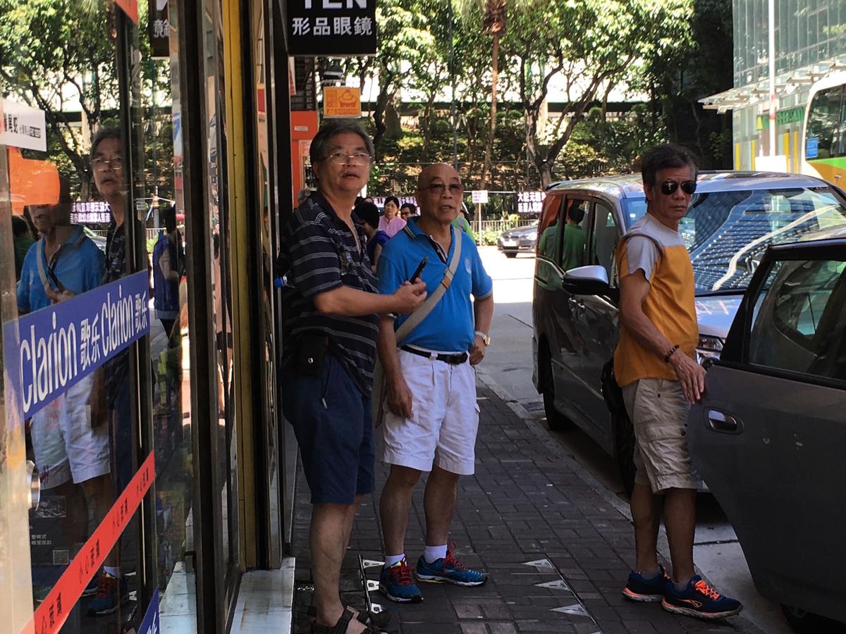 民交協會長許淵(左一)和成員郭亨溪(左二)駐紮看守。他們是連續第二天到場館外滋擾。(梁珍/大紀元)