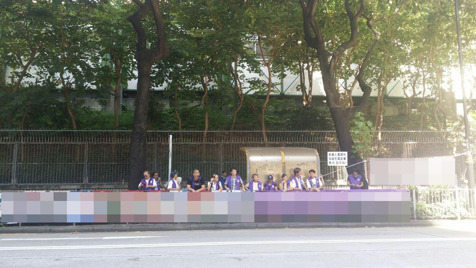 7月23日,中共外圍組織香港關注基層市民協會再在新唐人舉辦的「全世界中國古典舞大賽」亞太區初賽場館——麥花臣場館另一側對面的染布房街上,懸掛多幅污衊展板及橫幅。(余鋼/大紀元)