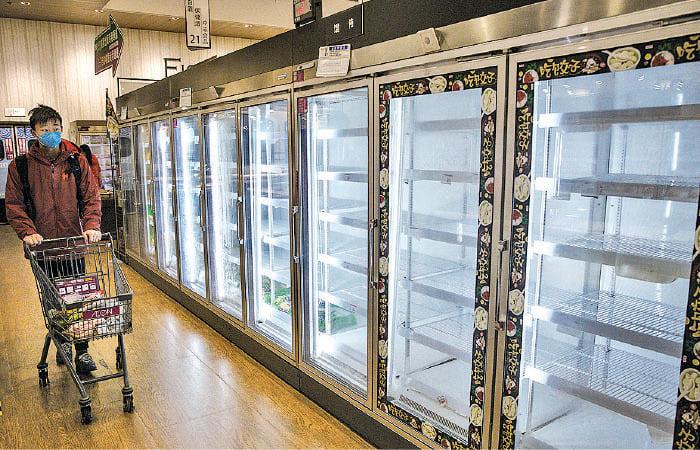 圖為2月12日,武漢封城下,海陸空交通停擺,超市的貨品被搶購一空,沒有貨品可補充。(Getty Images)