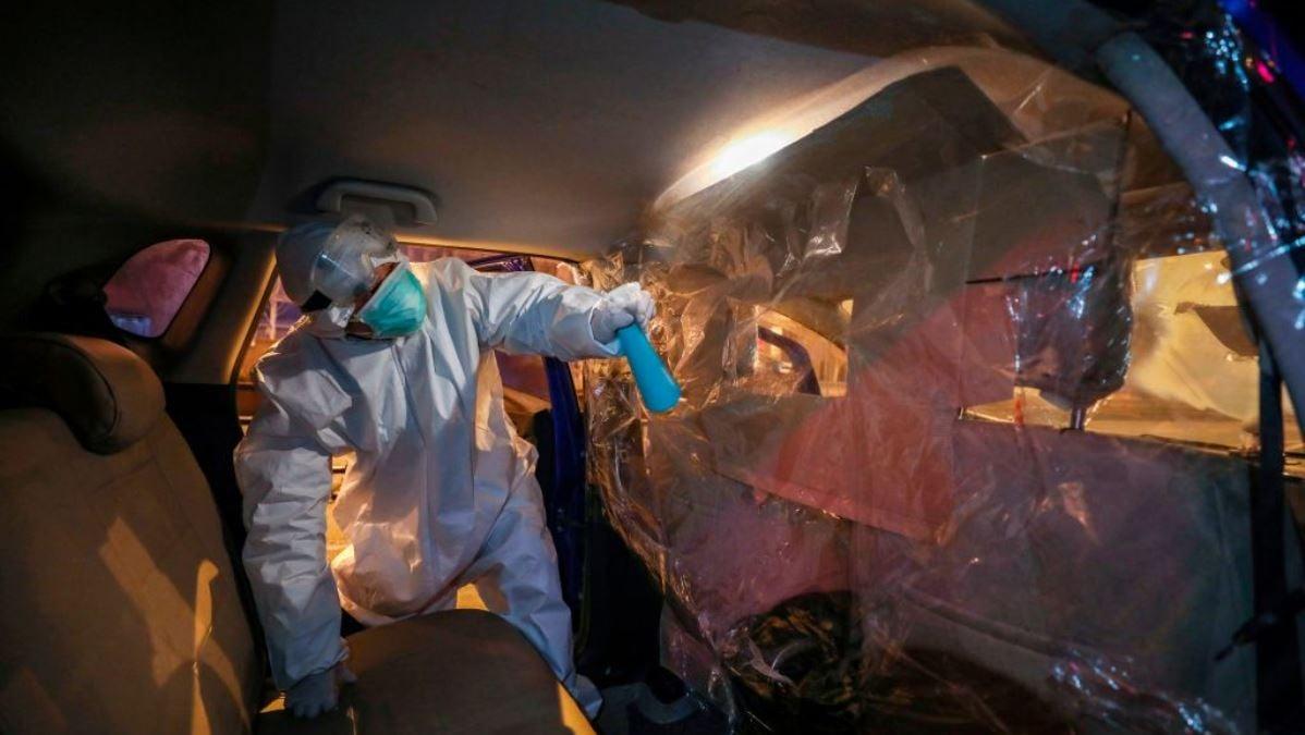 這張2020年2月22日拍攝的照片顯示,中國湖北省中部武漢市一名志願者在將一名中共肺炎(新冠肺炎)患者送到醫院後對其汽車進行了消毒。(STR/AFP via Getty Images)
