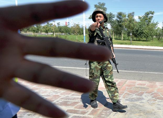 2013 年6 月,新疆一個檢查站,武警阻擋記者拍照。(AFP)