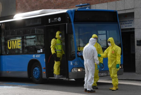 2020年3月29日,西班牙軍事緊急部隊(UME)成員穿著防護服站在公共汽車外面,該公共汽車用於將患者從聖卡洛斯診所醫院運送到馬德里的Ifema會議展覽中心的臨時醫院。(PIERRE-PHILIPPE MARCOU/AFP via Getty Images)
