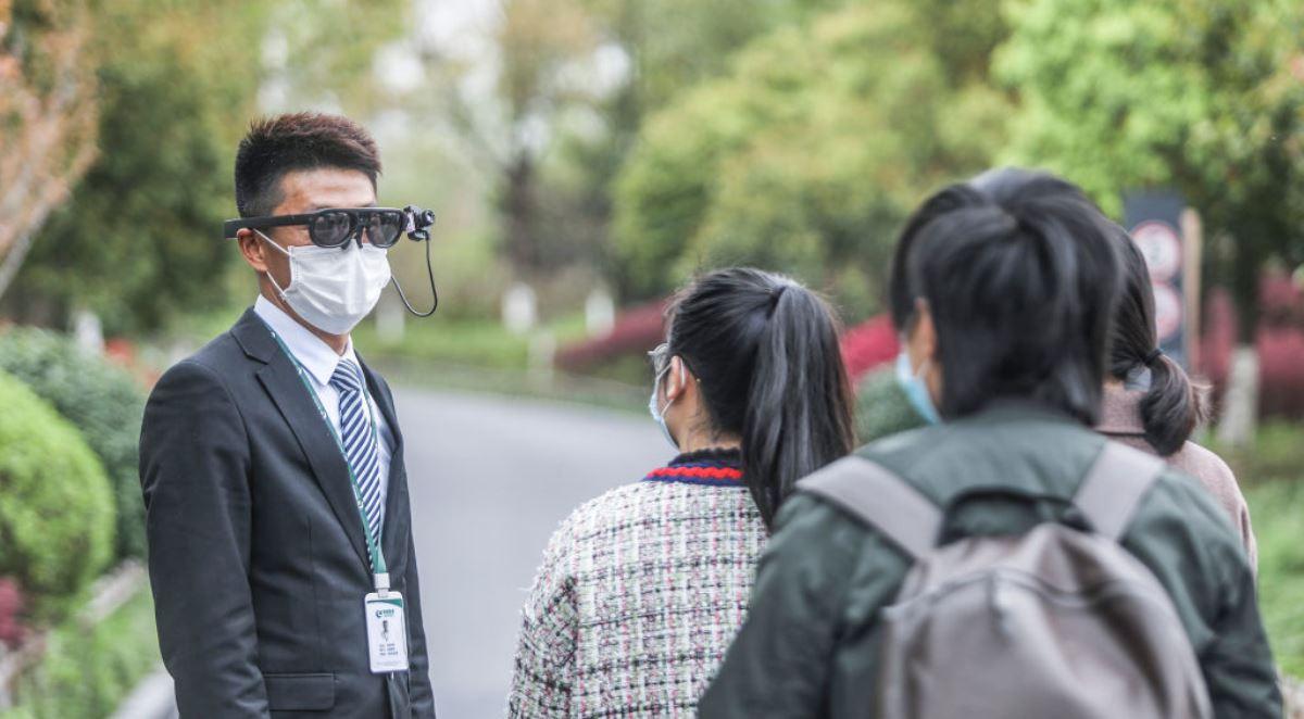 圖為2020年3月24日中國浙江省杭州市的一個公園中,戴著口罩和頭戴式AR裝置的保安人員正在給遊客測體溫。(STR/AFP via Getty Images)