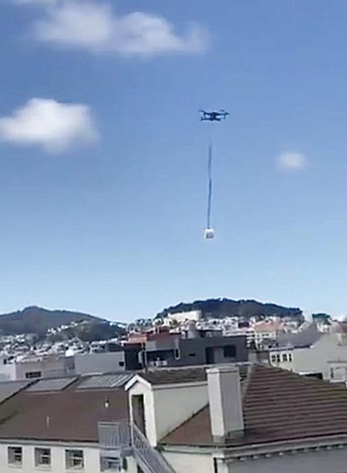 無人機正載著一卷廁紙飛越一片住宅區。(網上影片截圖)