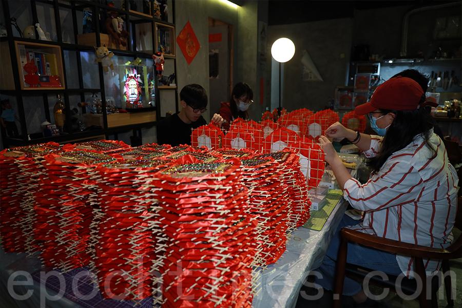 500個花牌在義工手下誕生,由「一班乖孫」的義工進行最後的組裝。(陳仲明/大紀元)