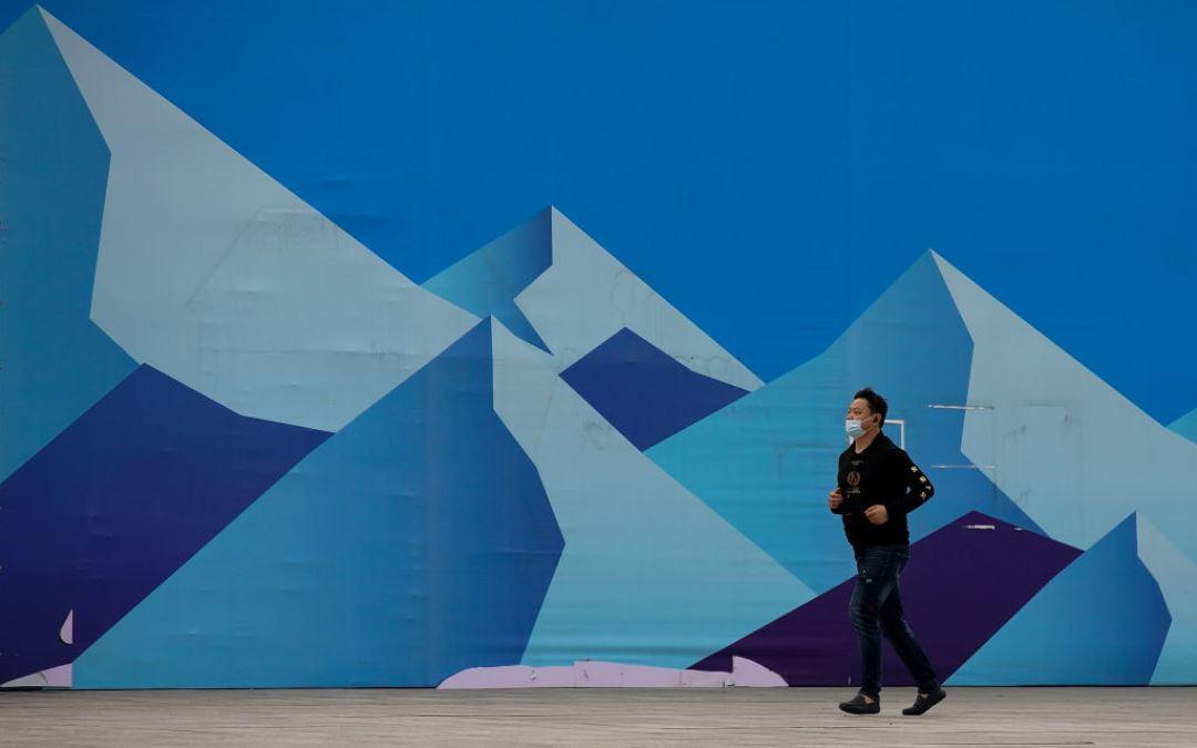 中共病毒在全球大流行之際,中國北京一名男子戴著防護口罩從巨型冰山的廣告佈景前跑過。(Lintao Zhang/Getty Images)