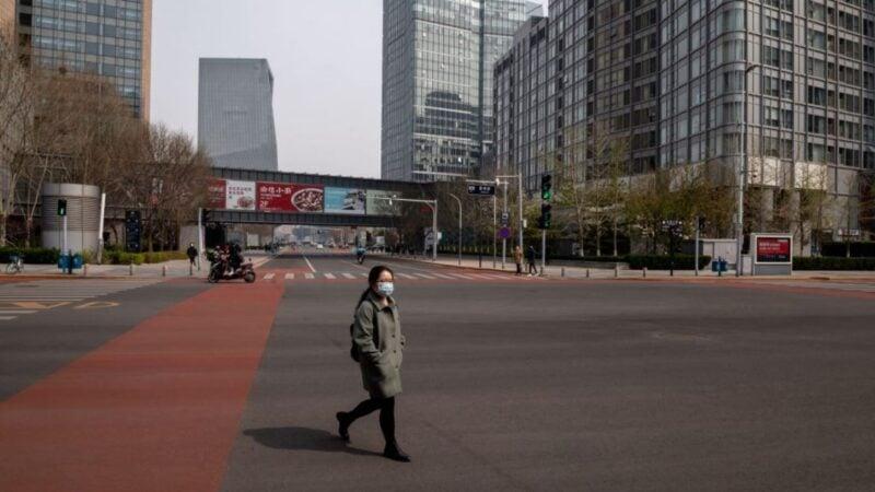 中共病毒(COVID-19)疫情在全球蔓延期間,2020年3月30日北京一名戴著口罩的婦女穿過冷清的十字路口。(NICOLAS ASFOURI/AFP via Getty Images)