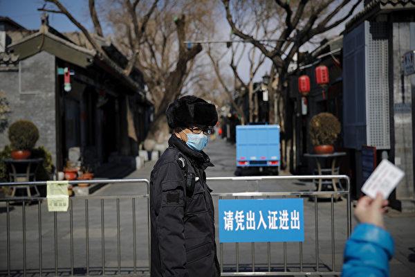近日,佳木斯地區疫情告急,通過物業管理中心再發緊急通知,各小區從新封閉式管理,再設卡點。圖為3月1日,北京一居民向小區保安出示證件。(加通社)