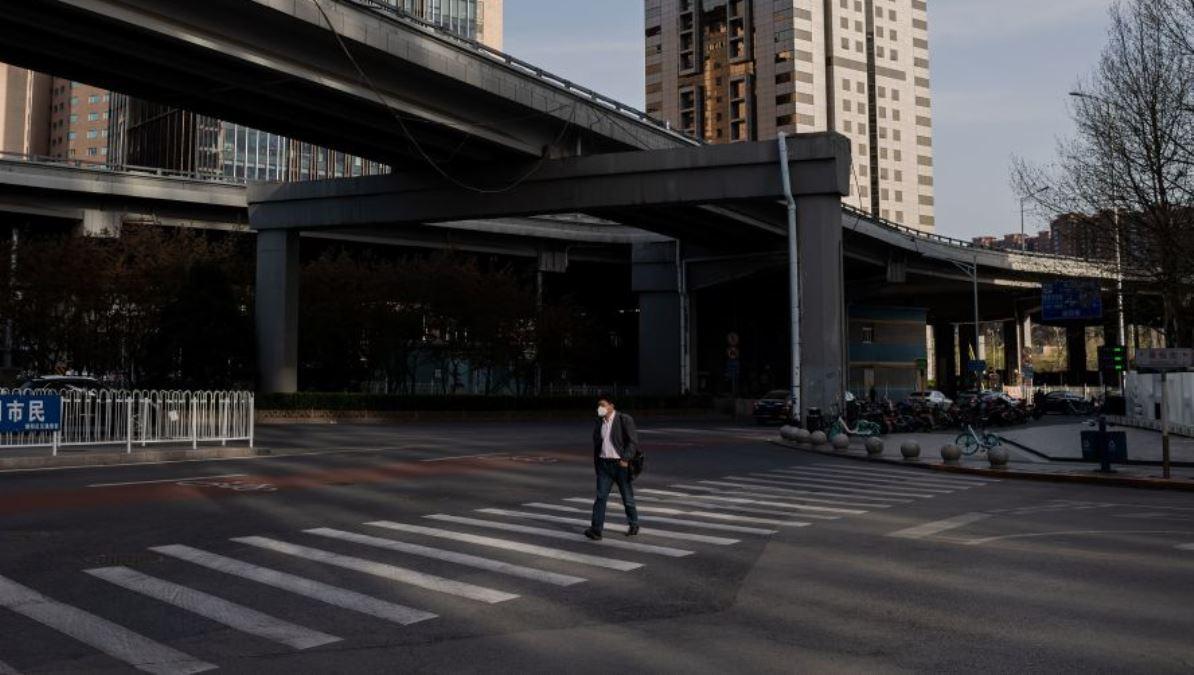 中共病毒(COVID-19)疫情期間,一名戴著口罩的中國男子2020年4月1日在北京空蕩盪的大街上穿過人行橫道。(NICOLAS ASFOURI/AFP via Getty Images)