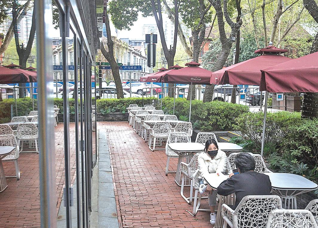 疫情爆發,讓武漢餐飲業損失慘重,近日武漢150餐館向政府請願。圖為4月1日,兩位武漢市民坐在一家餐館外面。(Getty Images)