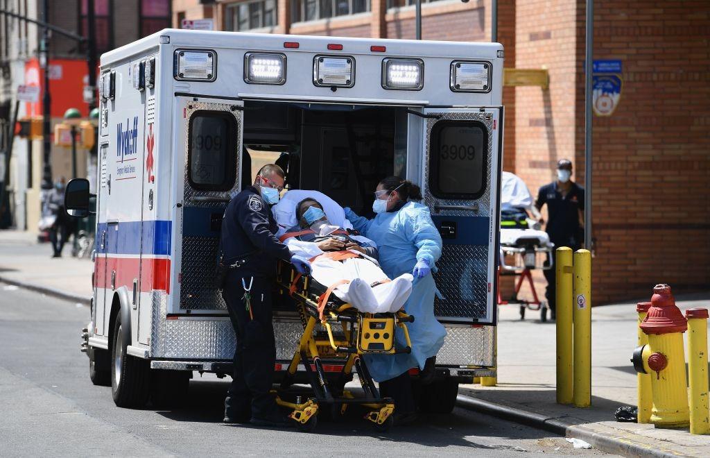 美國紐約疫情嚴峻,醫護人員正在把患者送上急救車。 (Photo by ANGELA WEISS/AFP via Getty Images)