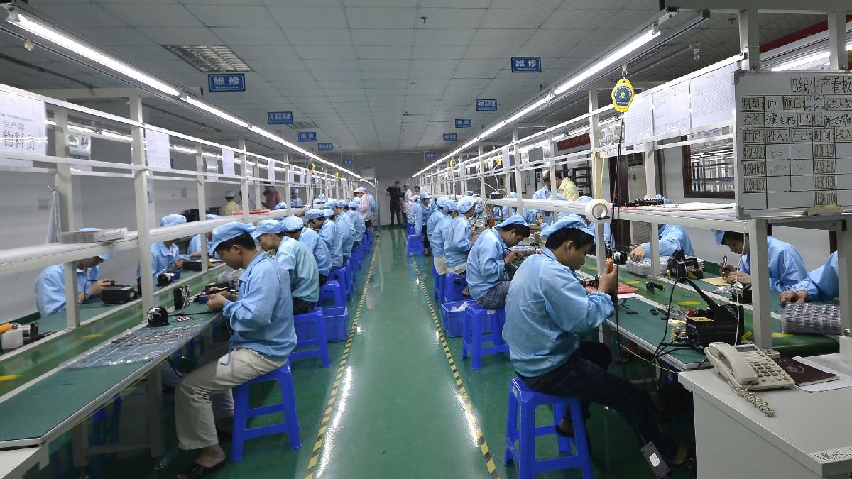2015年4月22日,在中國廣東省深圳市的一家工廠裏,工人們正在組裝一款價格更便宜的蘋果手錶替代品。(STR/AFP via Getty Images)