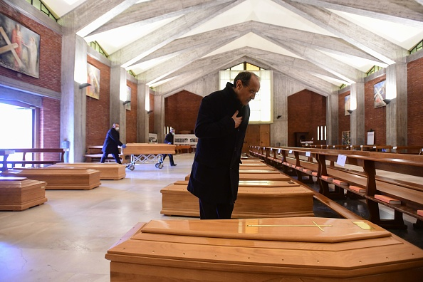 2020年3月26日,意大利處於封城時期。塞里特(Seriate)的聖朱塞佩(San Giuseppe)教堂裡存放著感染中共病毒死亡者的棺材,等待被軍車運走。神父站在其中一棺材旁禱告。 (PIERO CRUCIATTI/AFP via Getty Images)