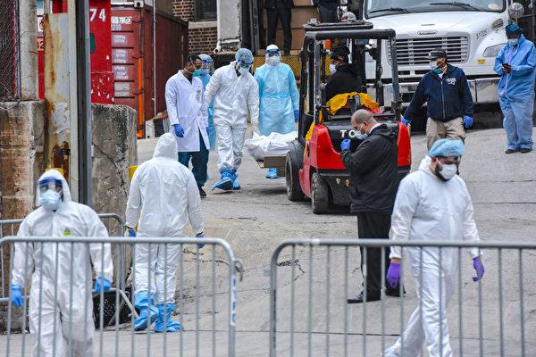 美國紐約因中共病毒(武漢肺炎)引起的死亡人數激增,多家醫院外都放置了冷藏卡車作為臨時停屍房。圖為布碌崙醫務人員在醫院外搬運屍體。 (Stephanie Keith/Getty Images)