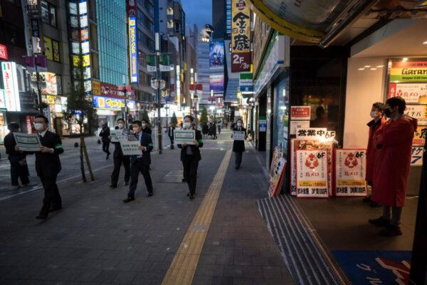 2020年4月11日,為遏止中共肺炎擴散,日本東京市政府職員戴口罩、拿著標誌,在歌舞伎町娛樂區,提醒民眾留在家。東京都知事小池百合子(Yuriko Koike)日前要求包括學校,體育設施,酒吧和餐館在內的企業在減少工作時間的情況下暫時關閉。(Tomohiro Ohsumi/Getty Images)