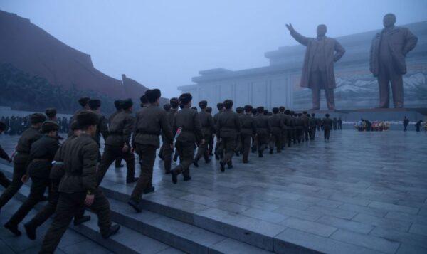 圖為平壤萬壽山一隊北韓士兵正走向金正日父子雕像,舉行政治性紀念活動。(KIM WON JIN/AFP via Getty Images)