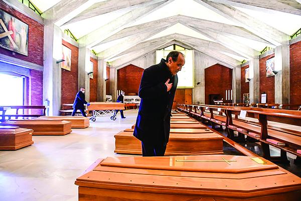 3月26日,意大利處於封城時期。教堂裏存放著感染中共病毒死亡者的棺材,等待被軍車運走。神父站在其中一棺材旁禱告。(Getty Images)