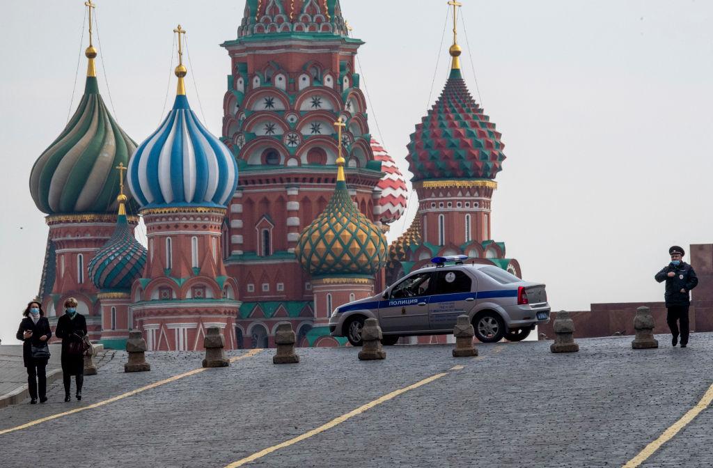 2020年4月13日,在俄羅斯嚴格封鎖期間,一名警務人員接近兩名在莫斯科市中心紅場上行走的婦女。(YURI KADOBNOV/AFP via Getty Images)