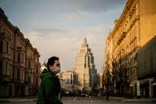一名戴著口罩的婦女13日在莫斯科市中心一個空無一人的街道上走動。(DIMITAR DILKOFF/AFP via Getty Images)