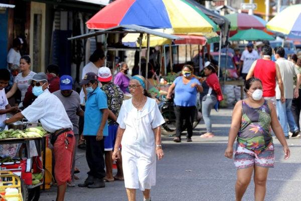 厄瓜多爾防疫隔離期間,儘管有軍人部署在街頭,小販沒戴口罩便在街上做生意的情況隨處可見,商店外的民眾也無視保持社交距離的建議。圖為2020年4月6日,隨處可見民眾,在街邊散步購物。(Francisco Macias/Getty Images)