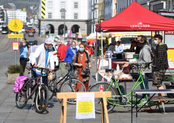2020年4月10日戴著口罩的人在奧地利林茨的主要廣場上的一個市場上購物。(HELMUT FOHRINGER/APA/AFP)