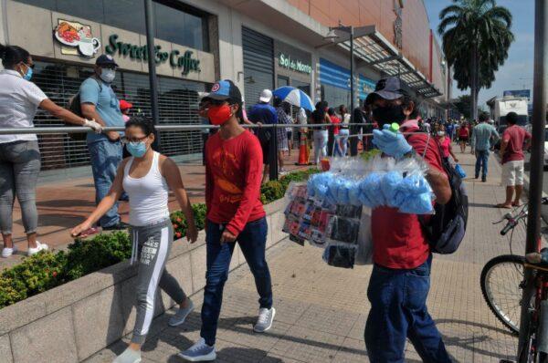 厄瓜多爾防疫隔離期間,儘管有軍人部署在街頭,小販沒戴口罩便在街上做生意的情況隨處可見,商店外的民眾也無視保持社交距離的建議。圖為2020年4月7日,隨處可見民眾,在街邊散步購物。(JOSE SANCHEZ/AFP via Getty Images)