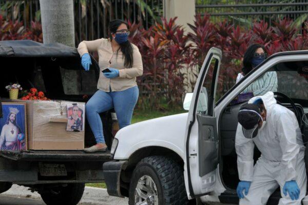 圖為,2020年4月9日,載著紙板棺材的車子,在墓地外的車輛大排長龍。(JOSE SANCHEZ/AFP via Getty Images)