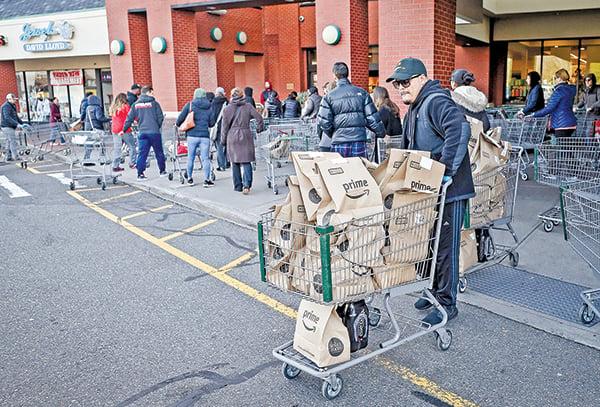 3月18日,紐約一家全食超市員工用推車運送亞馬遜會員訂購的商品。(Getty Images)