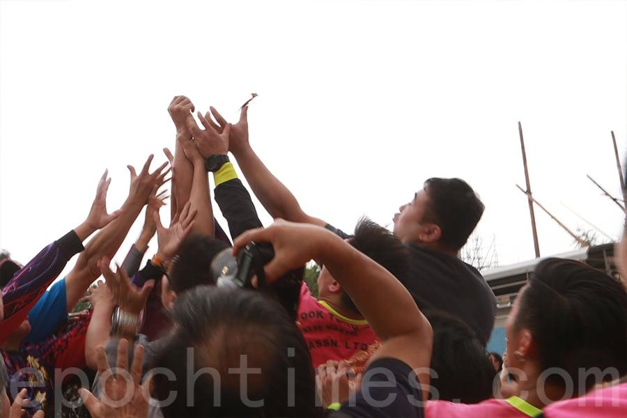 參加者在場地上伸手搶奪花炮,搶到花炮者舉手示意。(陳仲明/大紀元)