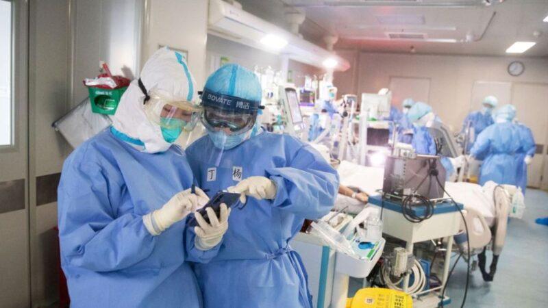 中國中部湖北省武漢市一家醫院的醫務人員2020年3月19日在為中共病毒肺炎(COVID-19)患者進行治療時察看手機。(STR/AFP via Getty Images)